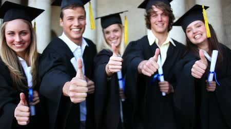 promoce : Students laughing while holding their diplomas in front of the university