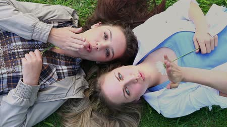 üfleme : Happy friends holding flowers while lying on the grass