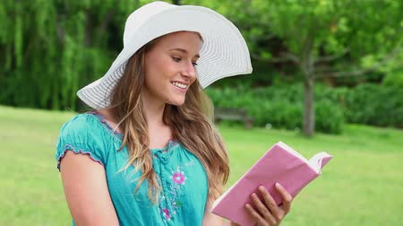 стоять : Happy young woman reading a fascinating book in the countryside