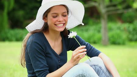 шляпа : Happy woman smelling a white flower in a park