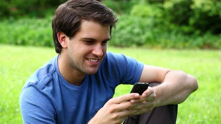 receber : Smiling man typing on his mobile phone in a park Stock Footage