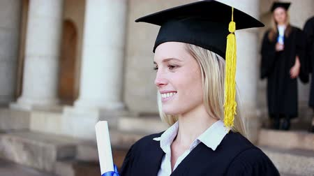 promoce : Smiling blonde student holding her diploma in front of the university