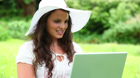 шляпа : Smiling brunette woman using her laptop in the countryside Стоковые видеозаписи