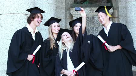 promoce : Graduates take self portrait together on front of the university Dostupné videozáznamy