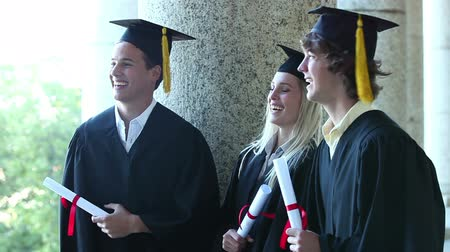 promoce : Trhee graduates laughing together while standing outsides