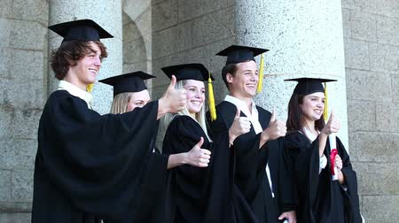 promoce : Graduates posing the thumbs-up in front of the university