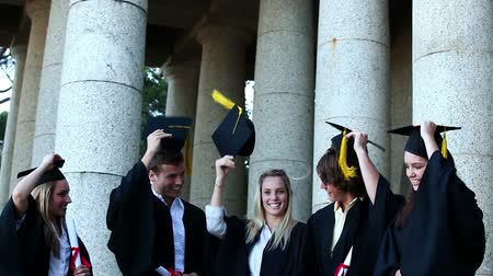 promoce : Graduates students throwing mortar boards in the air while holding diploma