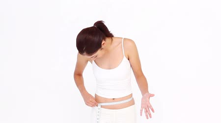 perda de peso : Brunette measuring her waist against white background