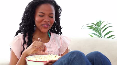 jeść : Woman eating popcorn while watching TV on a sofa