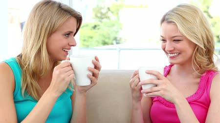 coffee time : Two blonde women drinking coffee while sitting on a sofa