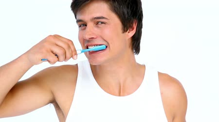 escovação : Man brushing and looking his teeth against white background