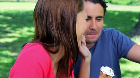 creams : Smiling couple eating ice creams while sitting on the grass in a parkland