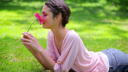 parque : Smiling young woman holding a pink flower while lying in a park