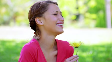 peaceful : Happy brunette woman holding a yellow flower in the countryside Stock Footage