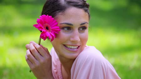 parky : Happy brunette woman holding a pink flower in a parkland