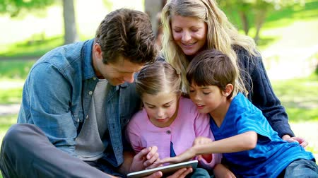 tabletler : Family using an ebook in a park
