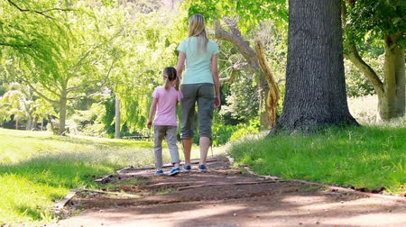 anne : Mother and daughter walking together in a park