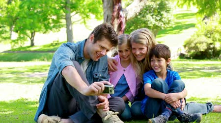 o : Family watching picture on a digital camera in a park