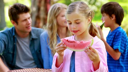 пикник : Girl eating a watermelon with her family in background in a park