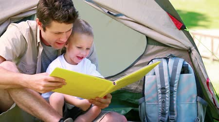 sátor : Man with his son looking picture book in front of a tent Stock mozgókép
