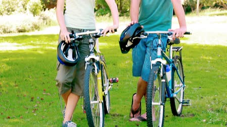 estilo de vida : Young couple standing with bikes in a park Vídeos
