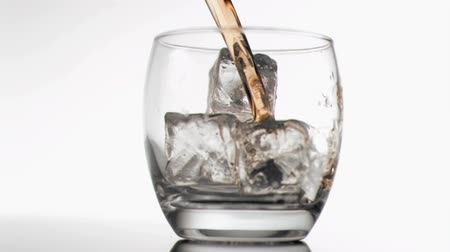 viski : Whiskey poured in super slow motion in a glass with ice against white background
