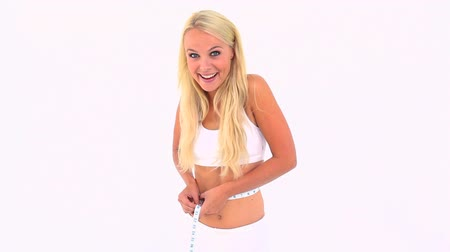 perda de peso : Blonde measuring her waist against white background