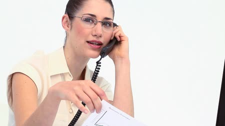 ношение : Businesswoman with glasses phoning at her desk against white background