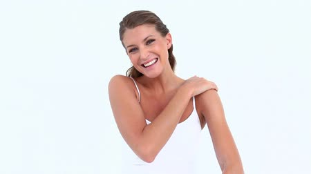 уход за кожей : Smiling woman applying moisturizer on her arm against white background