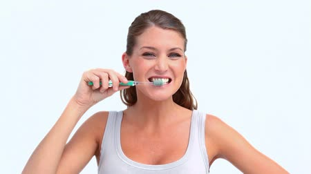 escovação : Woman brushing her teeth and smiling against white background Vídeos