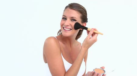 corar : Happy woman putting blush on her face against white background