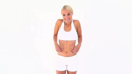 жир : Blonde shrugging her shoulders after touching her skinny belly against white background