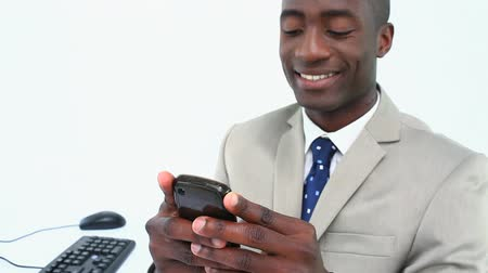 receber : Smiling man text-messaging against white background