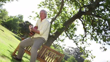 emekli : Retired man playing guitar suddenly stands up in a park