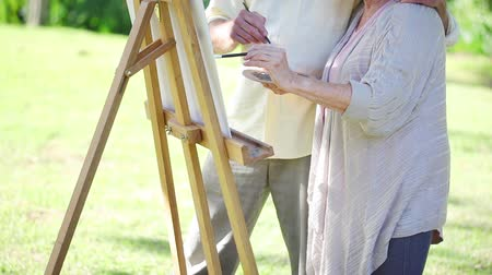 canvas : Retired couple painting together in a garden Stock Footage