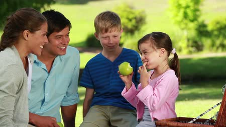 пикник : Little girl eating a green apple in front of her family in the countryside