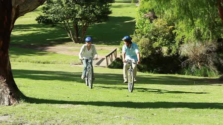 bisiklete binme : Happy couple riding their bikes together in a park