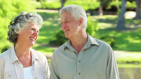 retirement : Smiling mature couple walking in front of a lake in the countryside