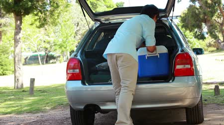 chladič : Rear view of a man placing his cooler in his car in a parking