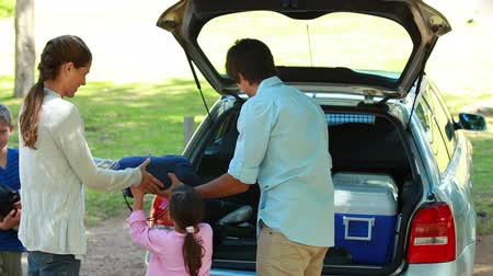 kamp : Father emptying the trunk of the car with his family on a parking