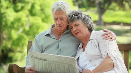 relação : Mature man reading a newspaper while embracing his wife in a parkland Stock Footage