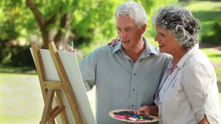 artistas : Smiling couple standing in front of a wooden easel in the countryside Vídeos
