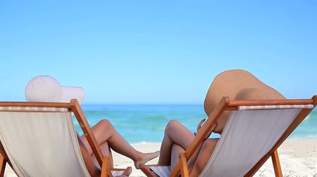 deck chairs : Peaceful woman resting while sitting on deck chairs on the beach Stock Footage