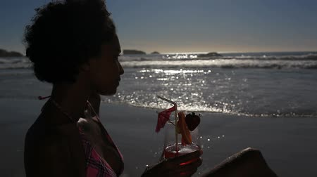 mehtap : Woman drinking her cocktail with a straw on the beach