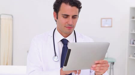 médicos : Serious doctor using his tablet pc in his office
