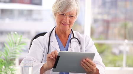 médicos : Smiling doctor using a tablet computer in a bright office Stock Footage