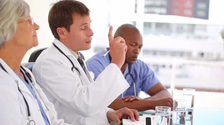 perguntando : Serious doctor raising his finger to ask a question in a bright office Stock Footage