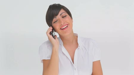 брюнет : Businesswoman talking on a phone against a white background Стоковые видеозаписи