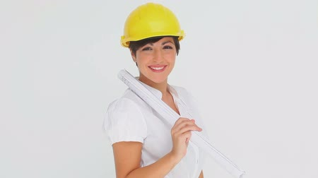 helmets : Businesswoman trying on a hard hat against a white background