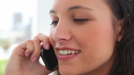 брюнет : Businesswoman smiling as she talks on a phone in an office